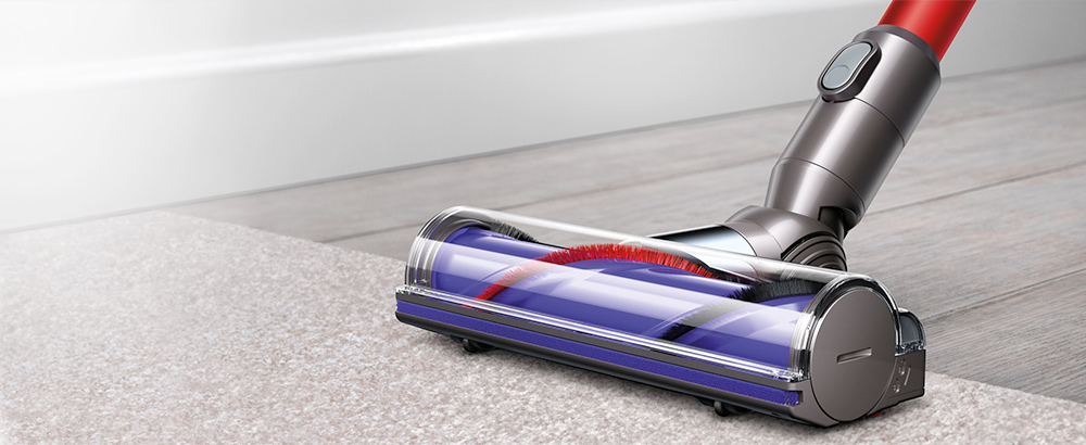 Close up of the Dyson V6 Cord-free vaccuum's motorised brush bar being used to collect hair and ground dirt from a carpet.